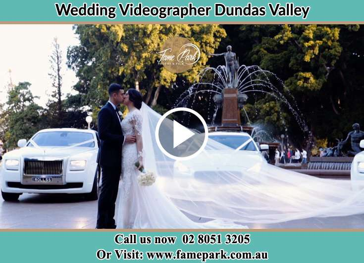 The new couple kissing near their wedding car Dundas Valley NSW 2117